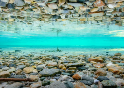reflection of pebbles in clear blue water